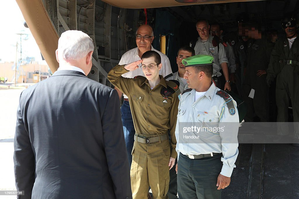 In this handout photo provided by the Israeli Defence Force, freed Israeli soldier <a gi-track='captionPersonalityLinkClicked' href=/galleries/search?phrase=Gilad+Shalit&family=editorial&specificpeople=537101 ng-click='$event.stopPropagation()'>Gilad Shalit</a> (C) salutes Israeli Prime Minister <a gi-track='captionPersonalityLinkClicked' href=/galleries/search?phrase=Benjamin+Netanyahu&family=editorial&specificpeople=118594 ng-click='$event.stopPropagation()'>Benjamin Netanyahu</a> at Tel Nof Airbase on October 18, 2011 in central Israel. Shalit was freed after being held captive for five years in Gaza by Hamas militants, in a deal which saw Israel releasing more than 1,000 Palestinian prisoners.