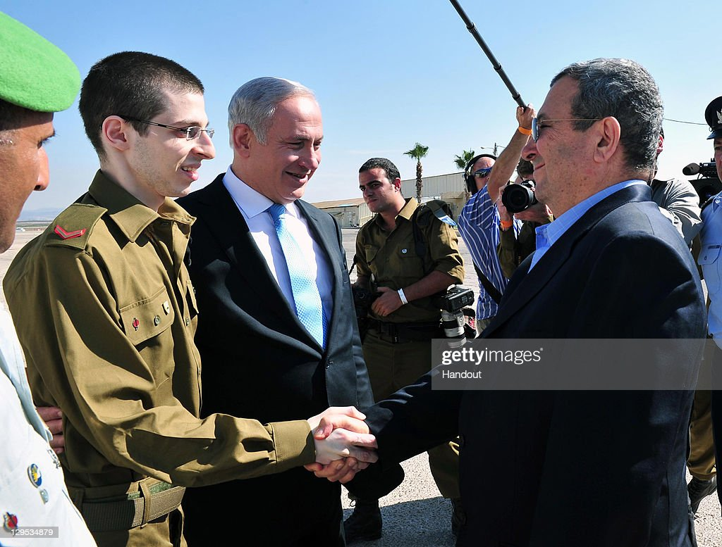 In this handout photo provided by the Israeli Defence Force, freed Israeli soldier <a gi-track='captionPersonalityLinkClicked' href=/galleries/search?phrase=Gilad+Shalit&family=editorial&specificpeople=537101 ng-click='$event.stopPropagation()'>Gilad Shalit</a> (L) shakes hands with Defence Minister <a gi-track='captionPersonalityLinkClicked' href=/galleries/search?phrase=Ehud+Barak&family=editorial&specificpeople=202888 ng-click='$event.stopPropagation()'>Ehud Barak</a> (R) next to Israeli Prime Minister <a gi-track='captionPersonalityLinkClicked' href=/galleries/search?phrase=Benjamin+Netanyahu&family=editorial&specificpeople=118594 ng-click='$event.stopPropagation()'>Benjamin Netanyahu</a> (C) at Tel Nof Airbase on October 18, 2011 in central Israel. Shalit was freed after being held captive for five years in Gaza by Hamas militants, in a deal which saw Israel releasing more than 1,000 Palestinian prisoners.