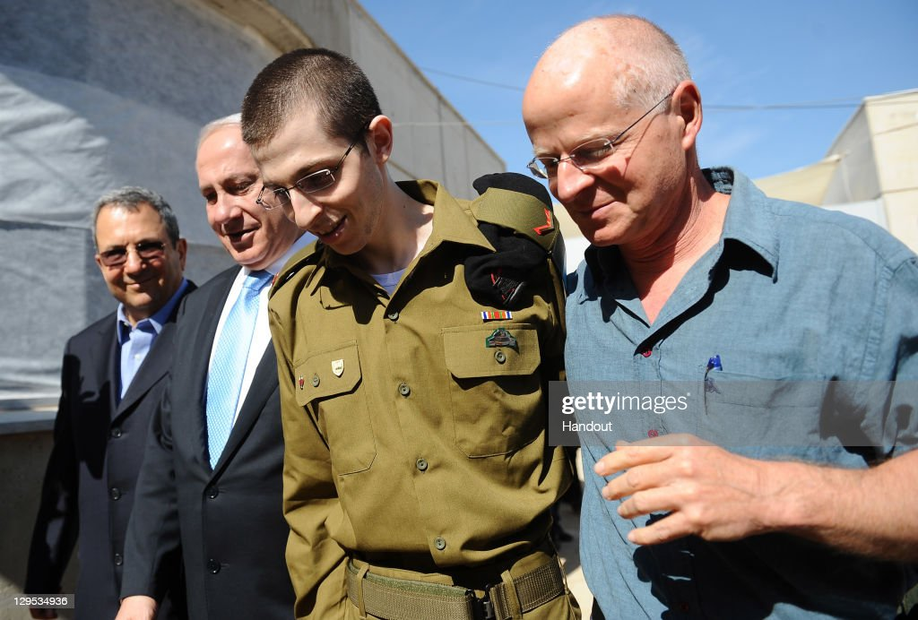 In this handout photo provided by the Israeli Defence Force, freed Israeli soldier <a gi-track='captionPersonalityLinkClicked' href=/galleries/search?phrase=Gilad+Shalit&family=editorial&specificpeople=537101 ng-click='$event.stopPropagation()'>Gilad Shalit</a> (2nd R) walks with (L-R) Defence Minister <a gi-track='captionPersonalityLinkClicked' href=/galleries/search?phrase=Ehud+Barak&family=editorial&specificpeople=202888 ng-click='$event.stopPropagation()'>Ehud Barak</a>, Israeli Prime Minister <a gi-track='captionPersonalityLinkClicked' href=/galleries/search?phrase=Benjamin+Netanyahu&family=editorial&specificpeople=118594 ng-click='$event.stopPropagation()'>Benjamin Netanyahu</a> his father Naom Shalit at Tel Nof Airbase on October 18, 2011 in central Israel. Shalit was freed after being held captive for five years in Gaza by Hamas militants, in a deal which saw Israel releasing more than 1,000 Palestinian prisoners.