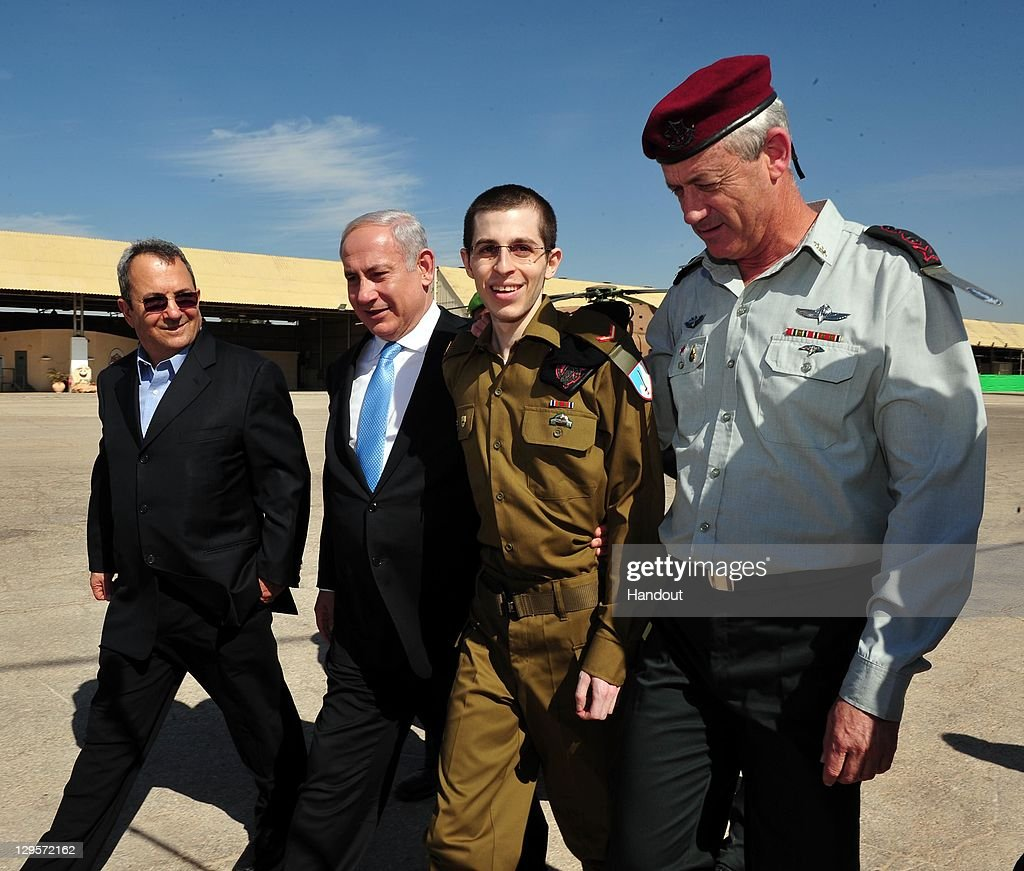 In this handout photo provided by the Israeli Defence Force, freed Israeli soldier <a gi-track='captionPersonalityLinkClicked' href=/galleries/search?phrase=Gilad+Shalit&family=editorial&specificpeople=537101 ng-click='$event.stopPropagation()'>Gilad Shalit</a> (2nd R) walks with Defence Minister <a gi-track='captionPersonalityLinkClicked' href=/galleries/search?phrase=Ehud+Barak&family=editorial&specificpeople=202888 ng-click='$event.stopPropagation()'>Ehud Barak</a> (L), Israeli Prime Minister <a gi-track='captionPersonalityLinkClicked' href=/galleries/search?phrase=Benjamin+Netanyahu&family=editorial&specificpeople=118594 ng-click='$event.stopPropagation()'>Benjamin Netanyahu</a> (2nd, L) and IDF Chief of General Staff Benny Gantz (R) at Tel Nof Airbase on October 18, 2011 in central Israel. Shalit was freed after being held captive for five years in Gaza by Hamas militants, in a deal which saw Israel releasing more than 1,000 Palestinian prisoners.
