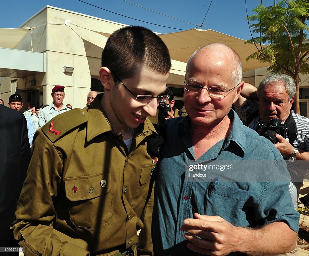 In this handout photo provided by the Israeli Defence Force, freed Israeli soldier <a gi-track='captionPersonalityLinkClicked' href=/galleries/search?phrase=Gilad+Shalit&family=editorial&specificpeople=537101 ng-click='$event.stopPropagation()'>Gilad Shalit</a> (L) walks with his father Naom Shalit at Tel Nof Airbase on October 18, 2011 in central Israel. Shalit was freed after being held captive for five years in Gaza by Hamas militants, in a deal which saw Israel releasing more than 1,000 Palestinian prisoners.