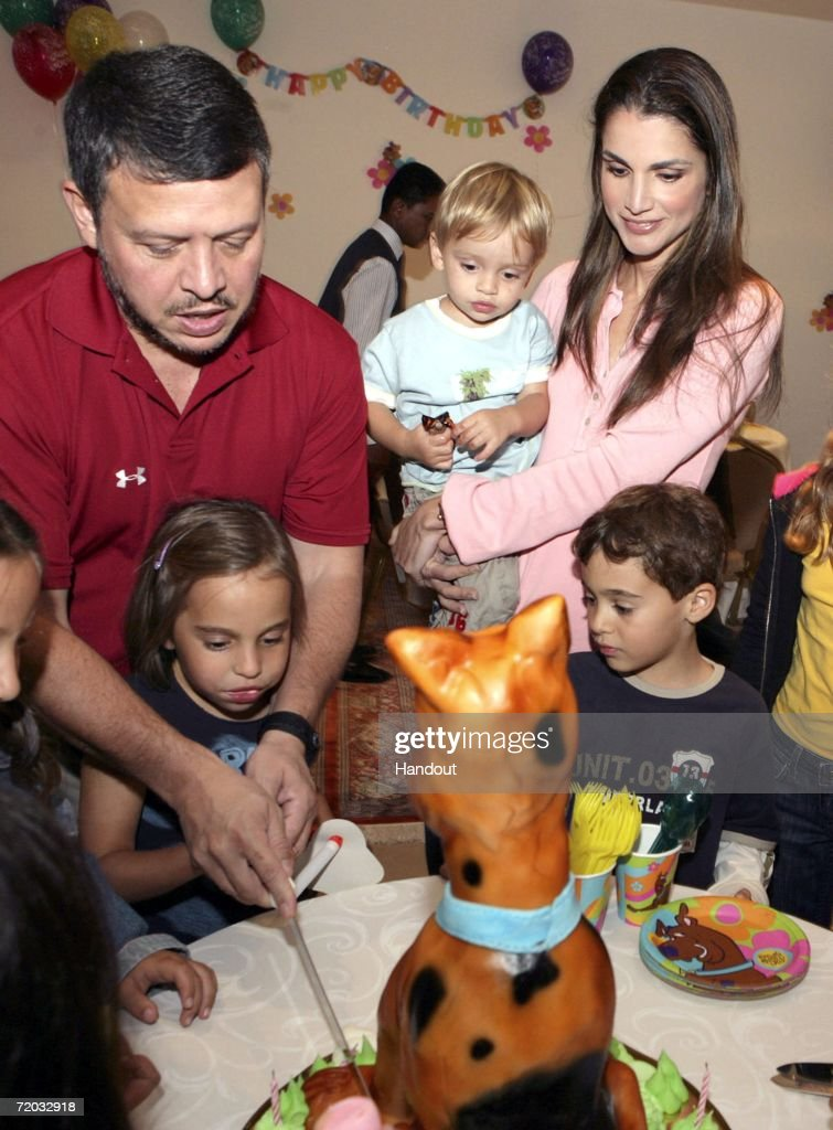 In this handout photo provided by the Jordanian Royal Palace His Majesty King Abdullah II bin Al Hussein helps his daughter Salma cut her birthday...