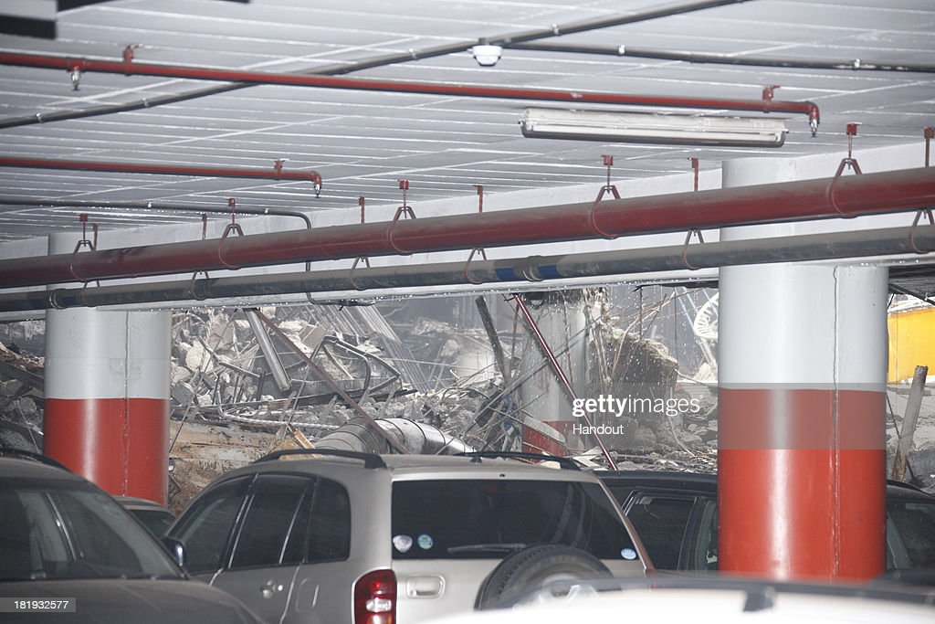 In this handout photo provided by the Kenyan Presidential Press Service, Cars are parked inside the parking garage near the debris of the Westgate Mall on September 26, 2013 in Nairobi, Kenya. The country is observing three days of national mourning as security forces begin the task of clearing and securing the Westgate shopping mall following a four-day siege by militants.