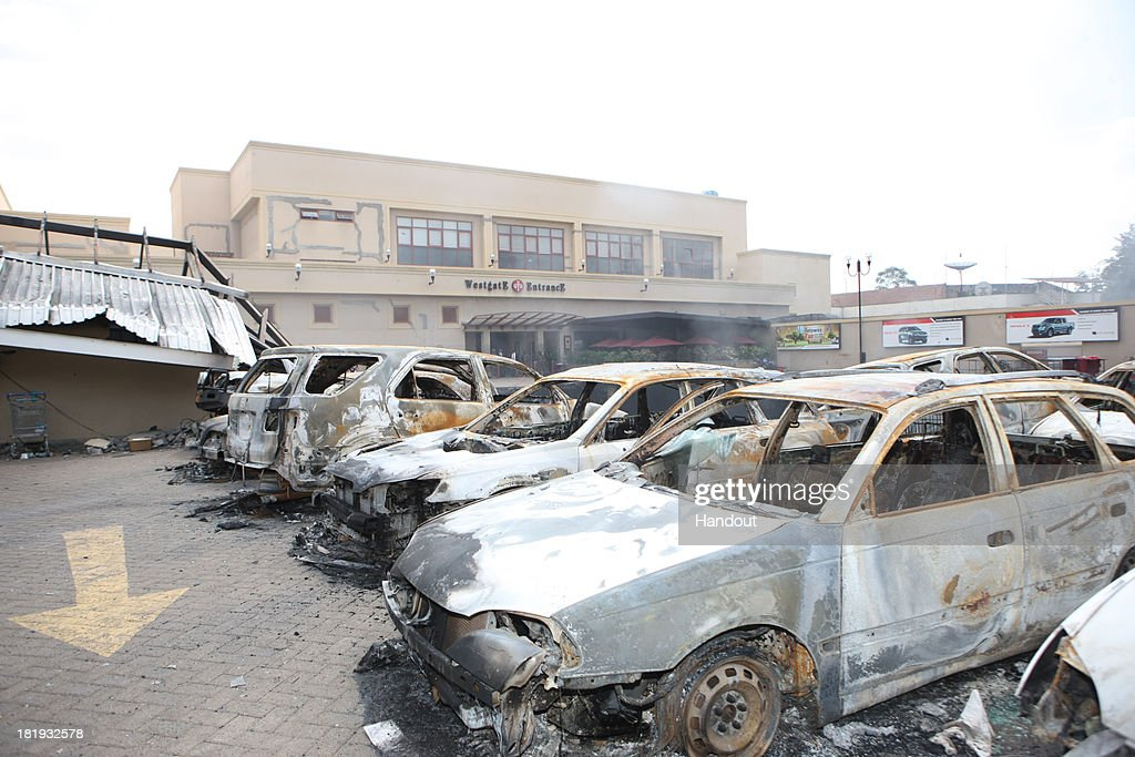 In this handout photo provided by the Kenyan Presidential Press Service, The remains of cars and other debris can be seen in a general view photographed outside the Westgate Mall on September 26, 2013 in Nairobi, Kenya. The country is observing three days of national mourning as security forces begin the task of clearing and securing the Westgate shopping mall following a four-day siege by militants.