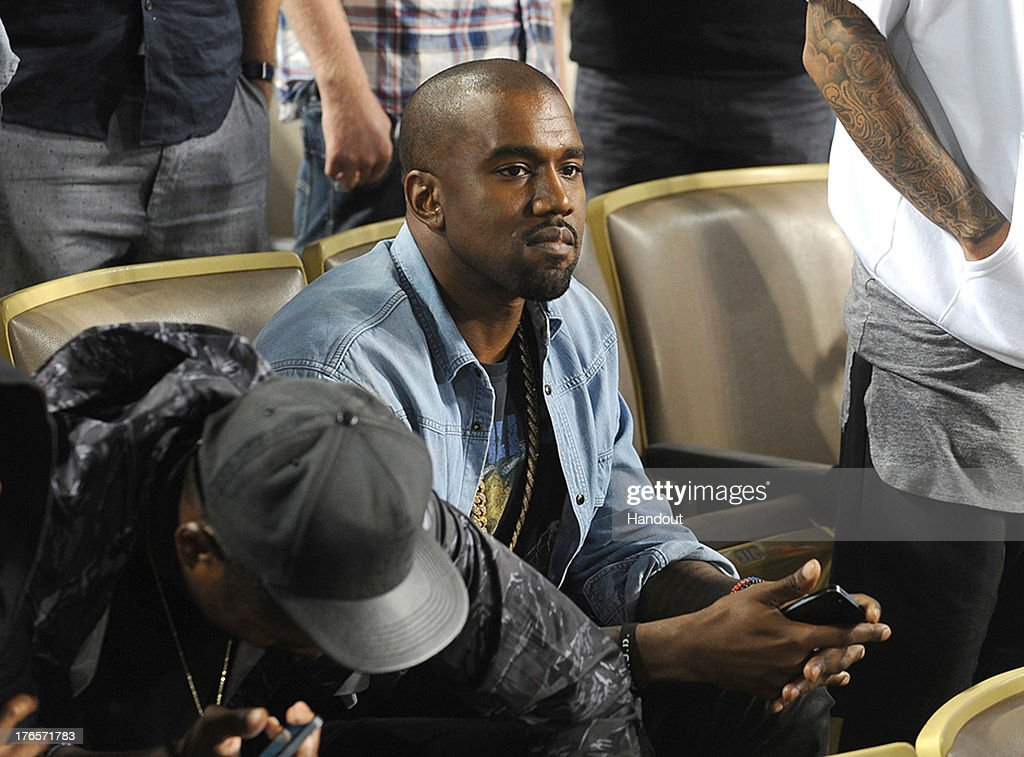 In this handout photo provided by the Los Angeles Dodgers, <a gi-track='captionPersonalityLinkClicked' href=/galleries/search?phrase=Kanye+West+-+Musician&family=editorial&specificpeople=201803 ng-click='$event.stopPropagation()'>Kanye West</a> attends the New York Mets v Los Angeles Dodgers game at Dodger Stadium on August 14, 2013 in Los Angeles, California.