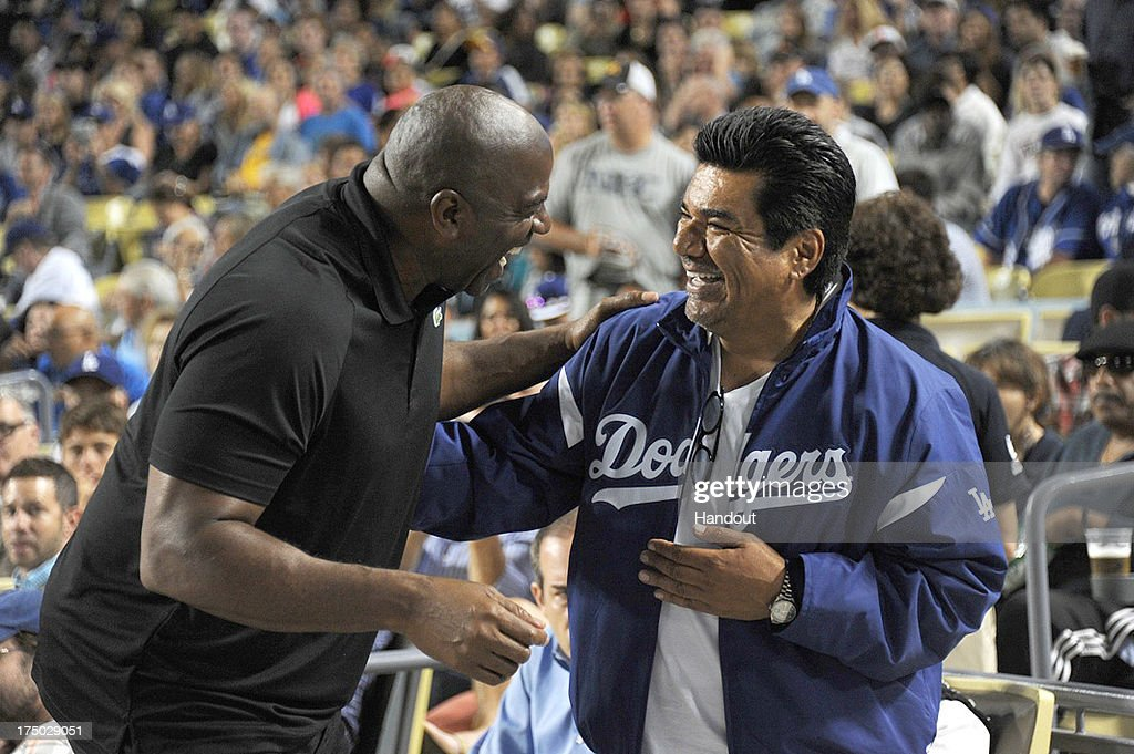 In this handout photo provided by the Los Angeles Dodgers, <a gi-track='captionPersonalityLinkClicked' href=/galleries/search?phrase=Magic+Johnson&family=editorial&specificpeople=157511 ng-click='$event.stopPropagation()'>Magic Johnson</a> and <a gi-track='captionPersonalityLinkClicked' href=/galleries/search?phrase=George+Lopez&family=editorial&specificpeople=202546 ng-click='$event.stopPropagation()'>George Lopez</a> attend the Cincinnatti Reds versus Los Angeles Dodgers game at Dodger Stadium on July 26, 2013 in Los Angeles, California.
