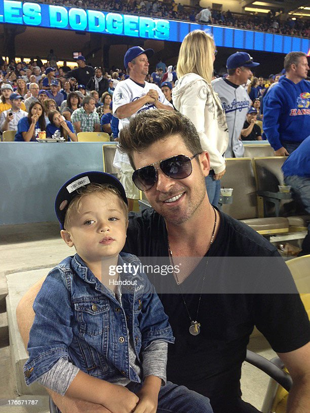 In this handout photo provided by the Los Angeles Dodgers, <a gi-track='captionPersonalityLinkClicked' href=/galleries/search?phrase=Robin+Thicke&family=editorial&specificpeople=724390 ng-click='$event.stopPropagation()'>Robin Thicke</a> (R) poses for a photo with son Julian Fuego Thicke at the New York Mets v Los Angeles Dodgers game at Dodger Stadium on August 14, 2013 in Los Angeles, California.