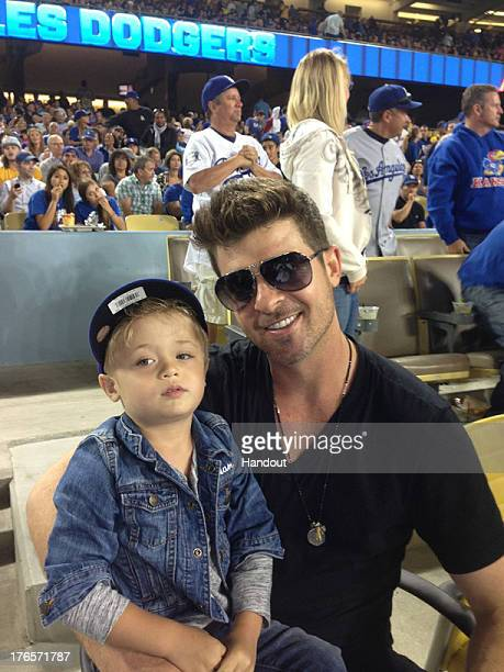 In this handout photo provided by the Los Angeles Dodgers Robin Thicke poses for a photo with son Julian Fuego Thicke at the New York Mets v Los...