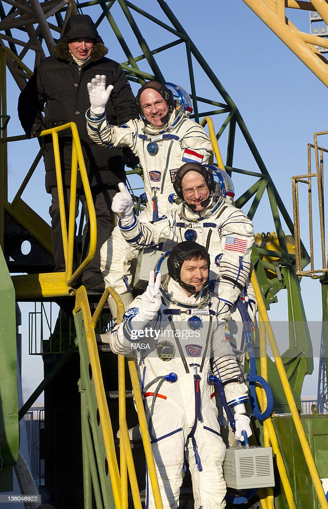 In this handout photo provided by the NASA, ESA Russian cosmonaut Oleg Kononenko, NASA astronaut Don Pettit and ESA astronaut André Kuipers wave goodbye to the crowd gathered at the foot of the Soyuz launch pad stairs before taking the elevator to the top of the Soyuz rocket on December 21, 2011 at Baikonur Cosmodrome in Kazakhstan. The Soyuz TMA-03M spacecraft is due to launch today from Baikonur Cosmodrome, ahead of a five month expedition to the International Space Station.