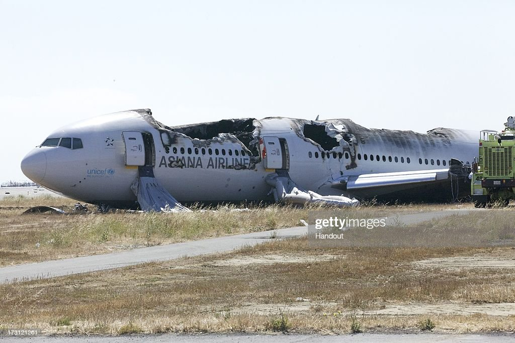 In this handout photo provided by the National Transportation Safety Board, the wreckage of Asiana Airlines flight 214 lies near the runway following yesterday's crash, on July 7, 2013 in San Francisco, California. The Boeing 777 passenger aircraft from Asiana Airlines coming from Seoul, South Korea crashed landed on the runway at San Francisco International Airport. Two people died and dozens were injured in the crash.
