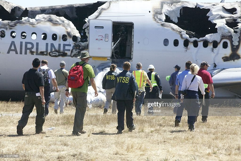 In this handout photo provided by the National Transportation Safety Board, NTSB investigators examine the wreckage of Asiana Airlines flight 214 following yesterday's crash, on July 7, 2013 in San Francisco, California. The Boeing 777 passenger aircraft from Asiana Airlines coming from Seoul, South Korea crashed landed on the runway at San Francisco International Airport. Two people died and dozens were injured in the crash.
