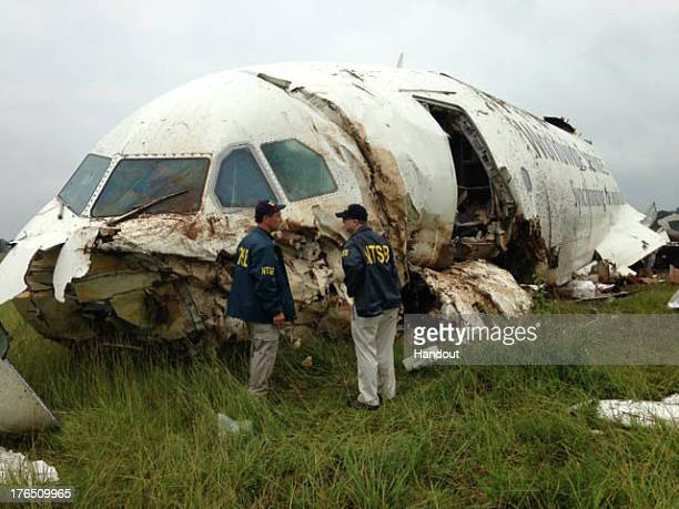 In this handout photo provided by the National Transportation Safety Board NTSB workers inspect the wreckage of a UPS cargo plane that crashed in a...