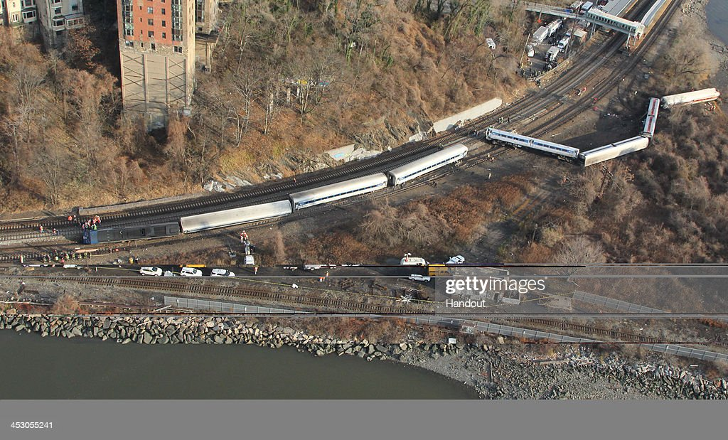 In this handout photo provided by the National Transportation Safety Board (NTSB), a Metro North train sits derailed December 01, 2013 in the Bronx borough of New York City. Multiple injuries and four deaths were reported after the seven car train left the tracks as it was heading to Grand Central Terminal along the Hudson River line.