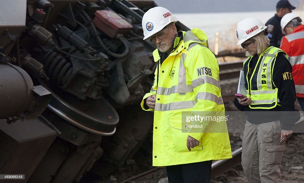 In this handout photo provided by the National Transportation Safety Board (NTSB), NTSB Investigator In Charge Michael Flanigon inspects the track after a Metro North train derailment December 01, 2013 in the Bronx borough of New York City. Multiple injuries and four deaths were reported after the seven car train left the tracks as it was heading to Grand Central Terminal along the Hudson River line.