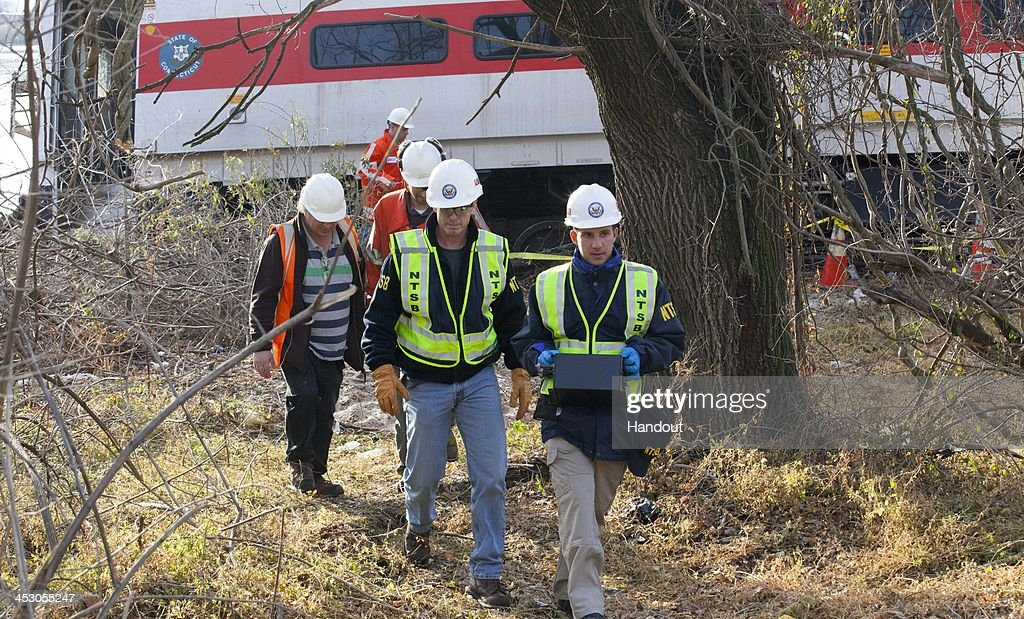 In this handout photo provided by the National Transportation Safety Board (NTSB), NTSB investigators carry an event recorder from the derailed Metro North train December 01, 2013 in the Bronx borough of New York City. Multiple injuries and four deaths were reported after the seven car train left the tracks as it was heading to Grand Central Terminal along the Hudson River line.