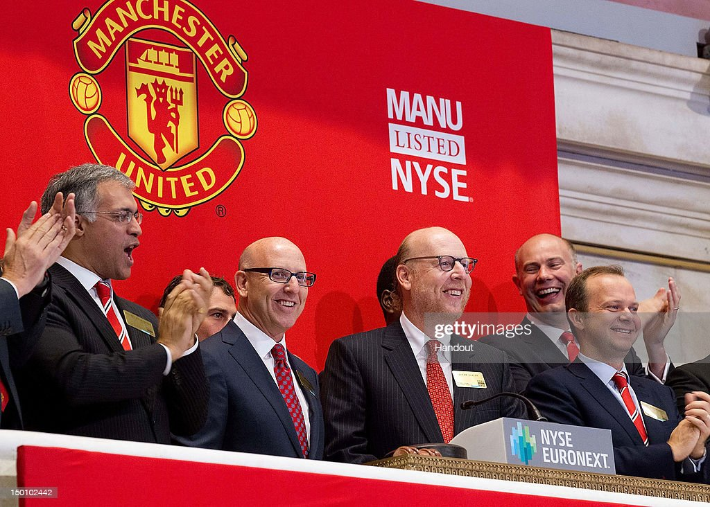 In this handout photo provided by the NYSE Euronext, Manchester United Executives Joel Glazer (2nd L) and Avram Glazer (C) and Ed Woodward prepare to ring the Opening Bell at the New York Stock Exchange on August 10, 2012 in New York City. Manchester United shares started trading at USD 14.05 at the opening of the New York Stock Exchange.