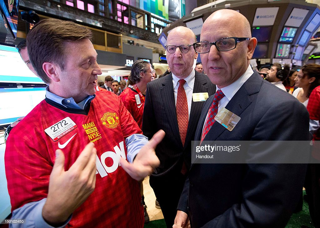 In this handout photo provided by the NYSE Euronext, Manchester United Executives Joel Glazer (R) and Avram Glazer (C) arrive to ring the Opening Bell at the New York Stock Exchange on August 10, 2012 in New York City. Manchester United shares started trading at USD 14.05 at the opening of the New York Stock Exchange.