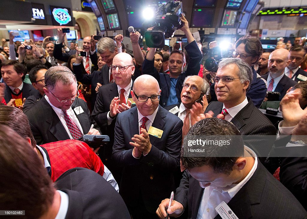 In this handout photo provided by the NYSE Euronext, Manchester United Executives Joel Glazer (C) and Avram Glazer (C,L) prepare to ring the Opening Bell at the New York Stock Exchange on August 10, 2012 in New York City. Manchester United shares started trading at USD 14.05 at the opening of the New York Stock Exchange.
