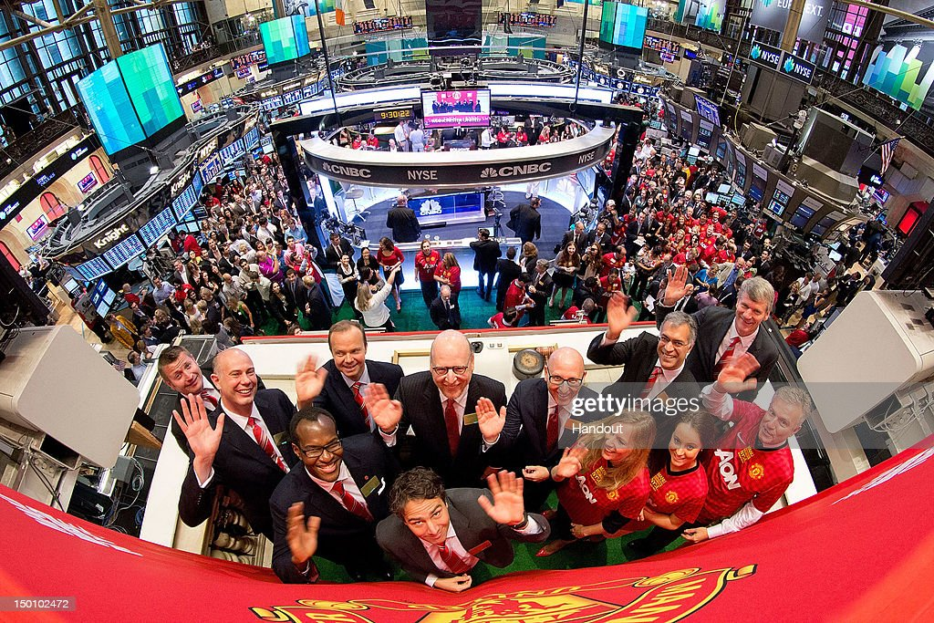 In this handout photo provided by the NYSE Euronext, Manchester United Executives David Gill (R), Joel Glazer (C, R) and Avram Glazer (C) with Ed Woodward prepare to ring the Opening Bell at the New York Stock Exchange on August 10, 2012 in New York City. Manchester United shares started trading at USD 14.05 at the opening of the New York Stock Exchange.