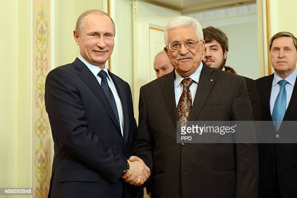 In this handout photo provided by the Palestinian Press Office Palestinian President Mahmoud Abbas and Russian President Vladimir Putin hold a...
