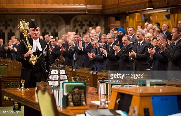 In this handout photo provided by the PMO Prime Minister Stephen Harper and all Members of Parliament applaud Kevin Vickers SergeantatArms during the...