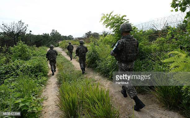 In this handout photo provided by the South Korean Defense Ministry on August 10 South Korean soldiers patrol near the scene where planted landmines...