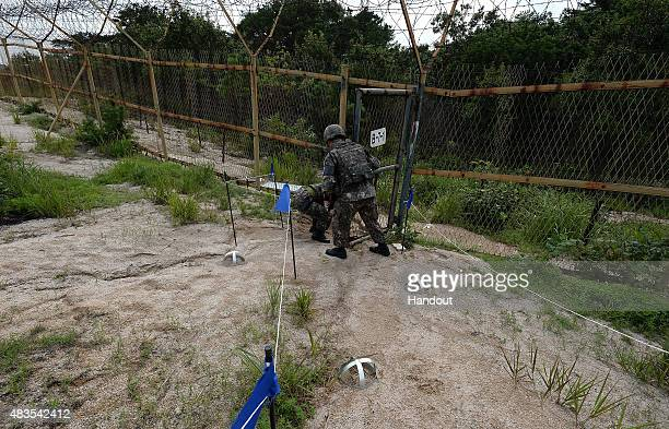 In this handout photo provided by the South Korean Defense Ministry on August 10 South Korean soldiers inspecting the scene where planted landmines...