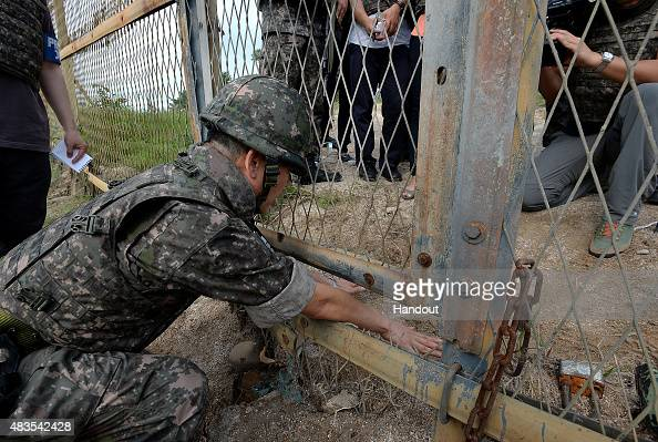 In this handout photo provided by the South Korean Defense Ministry on August 10 South Korean soldiers shows journalists visiting the scene where...