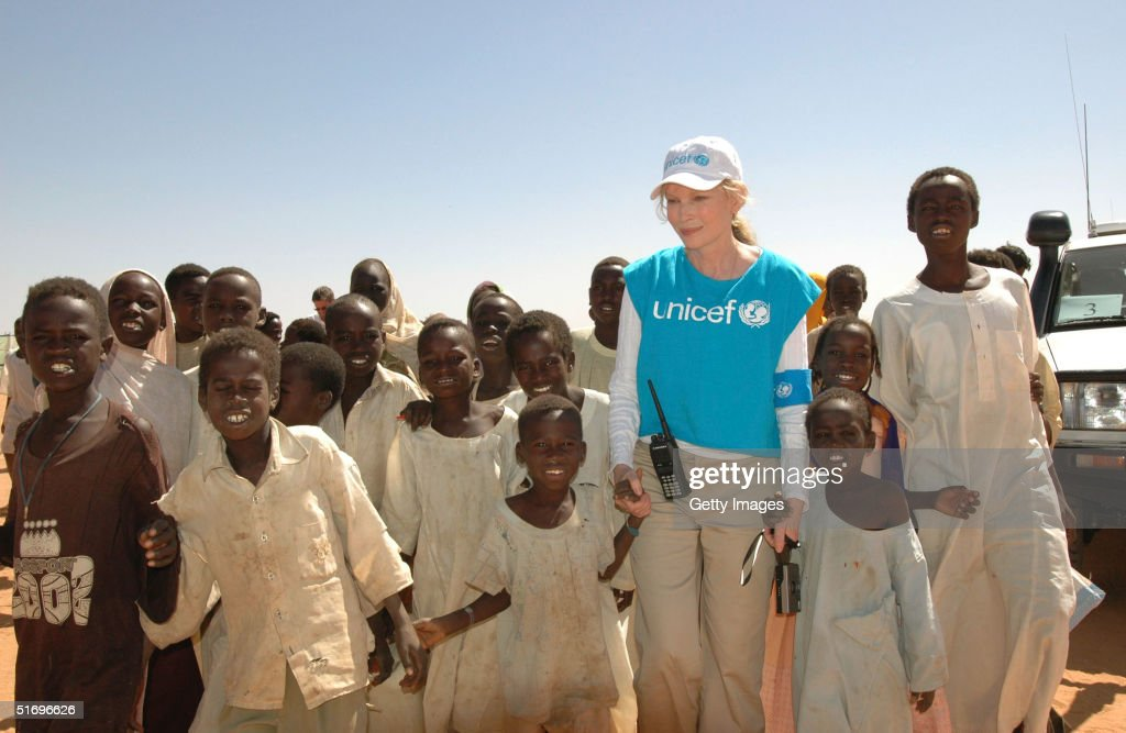 In this handout photo provided by the United Nations Children's Fund (UNICEF), actress Mia Farrow, a UNICEF goodwill ambassador, walks with Sudanese children in the IDP (Internally Displaced People) camp of Abu Shouk November 7, 2004 near Al Fasher city in Darfur, Sudan.