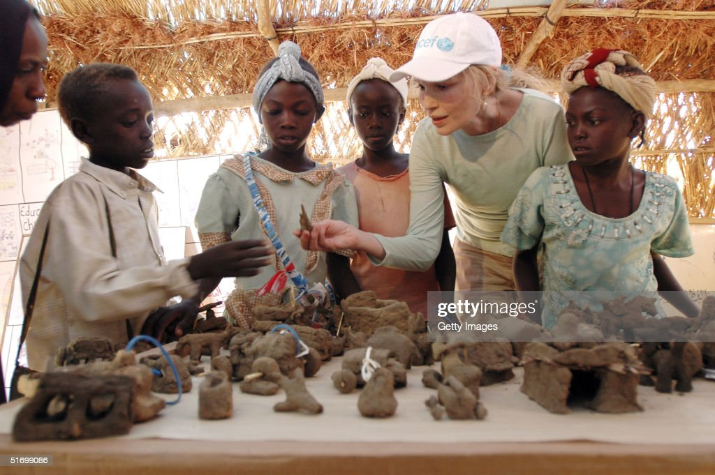 In this handout photo provided by the United Nations Children's Fund (UNICEF), actress Mia Farrow, a UNICEF goodwill ambassador, (2nd-R) is surrounded by children as she looks at clay toys that children in a ?Safe Play Centre? have made on November 8, 2004 in the Kalma camp for displaced people, near the city of Nyala, capital of South Darfur.