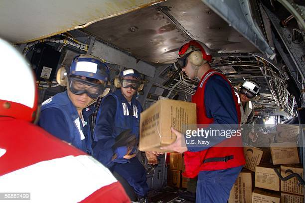 In this handout photo provided by the US Navy sailors and Marines load relief supplies aboard a CH46E Sea Knight assigned to the Flying Tigers of...