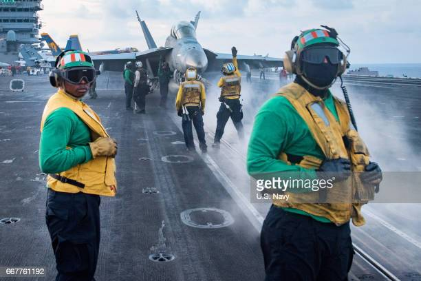 In this handout photo provided by the US Navy Sailors conduct flight operations on the aircraft carrier USS Carl Vinson flight deck The Carl Vinson...