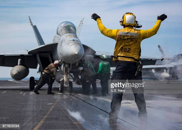 In this handout photo provided by the US Navy Sailors conduct flight operations Tuesday May 2 2017 aboard the Nimitzclass aircraft carrier USS Carl...