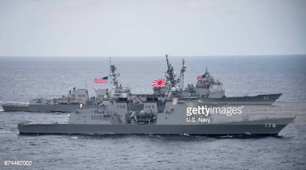 In this handout photo provided by the US Navy the Japan Maritime SelfDefense Force destroyer JS Ashigara foreground the Arleigh Burkeclass...