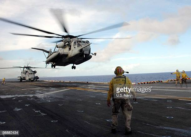 In this handout photo provided by the US Navy two CH53E Super Stallions belonging to Marine Air Combat Element 262 depart the flight deck carrying...