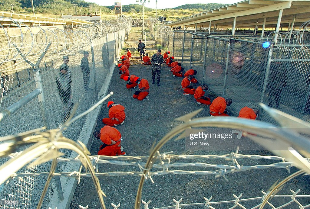 In this handout photo provided by the US Navy US Military Police guard Taliban and al Qaeda detainees in orange jumpsuits January 11 2002 in a...