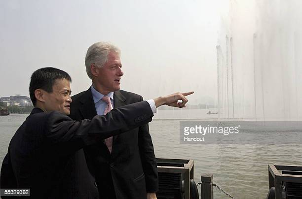 In this handout photo provided by the WCPV Jack Ma the CEO of Alibabacom shows former US president Bill Clinton around Hangzhou's West Lake during...