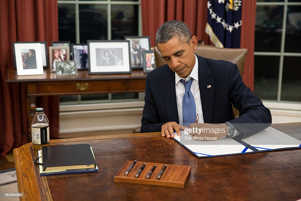 In this handout photo provided by The White House, U.S. President Barack Obama signs H.R. 3210, Pay Our Military Act, which provides continuing appropriations for pay and allowances for members of the Armed Forces during any period for which interim or full-year appropriations for FY 2014 are not in effect, in the Oval Office on September 30, 2013 in Washington, DC. If House Republicans do not find common ground with President Obama and Senate Democrats on the federal budget then at midnight large sections of the government will close, hundreds of thousands of workers would be furloughed without pay, and millions more would be asked to work for no pay.