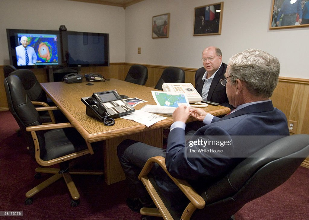 In this handout photo provided by the White House, U.S. President George W. Bush (foreground) takes a map from Deputy Chief of Staff Joe Hagin during a video teleconference with federal and state emergency management organizations on Hurricane Katrina August 28, 2005 at Bush's ranch in Crawford, Texas. The storm is expected to make landfall in Louisiana in the morning of August 29.