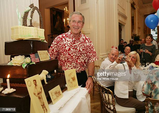 In this handout photo provided by the White House US President George W Bush is presented with a birthday cake during a dinner party at the White...
