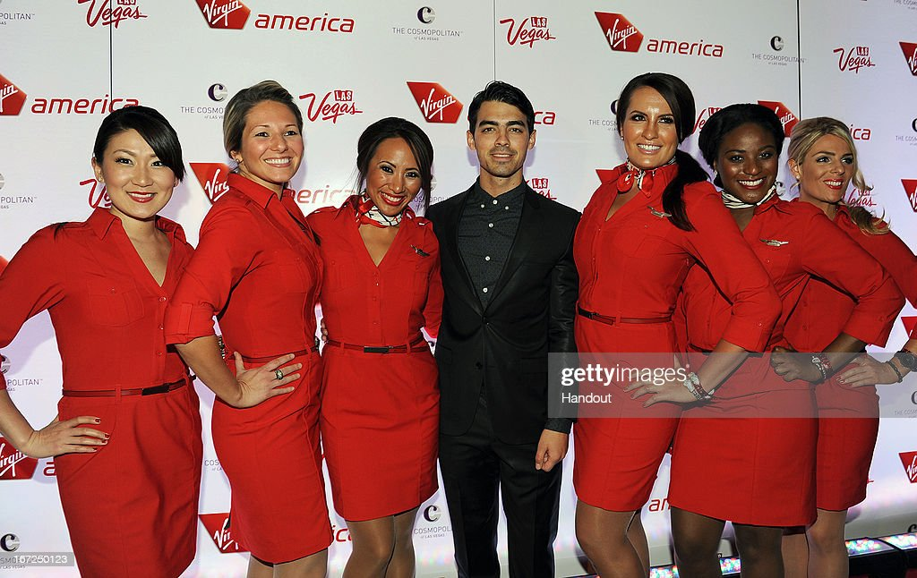 In this handout photo provided by Virgin America Airlines, Joe Jonas (C) is joined by Virgin America teammates on the red carpet during celebration of launch of new nonstop service from Los Angeles International (LAX) to Las Vegas McCarran International (LAS) Airports, Monday, April 22, 2013, inside The Chandelier at The Cosmopolitan of Las Vegas. The airline celebrates its new flight service with a launch party at The Chandelier at The Cosmopolitan of Las Vegas. The new three daily roundtrip flights from LAX to LAS will add to the airline's existing service from San Francisco and New York to Las Vegas.