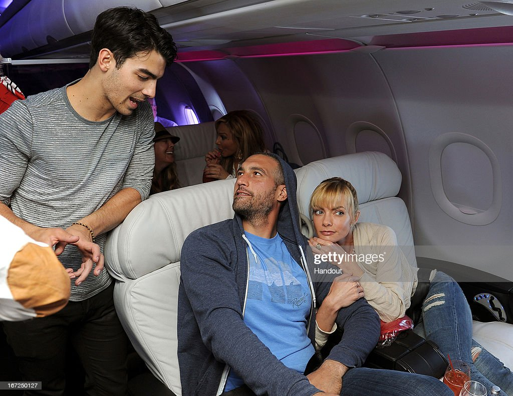 In this handout photo provided by Virgin America Airlines, musician <a gi-track='captionPersonalityLinkClicked' href=/galleries/search?phrase=Joe+Jonas&family=editorial&specificpeople=842712 ng-click='$event.stopPropagation()'>Joe Jonas</a> speaks with actress <a gi-track='captionPersonalityLinkClicked' href=/galleries/search?phrase=Jaime+Pressly&family=editorial&specificpeople=211226 ng-click='$event.stopPropagation()'>Jaime Pressly</a> and Hamzi Hijazi (c) in-flight during the launch of Virgin America's new nonstop service from Los Angeles International (LAX) to Las Vegas McCarran International (LAS) Airport on Monday, April 22, 2013 at LAX in Los Angeles. To mark the expansion of its Vegas routes, the airline launched a new seat-to-seat cocktail delivery service on flights nationwide, so travelers can send fellow guests onboard a drink and text message via a seatmap on the airline's in-flight entertainment platform.