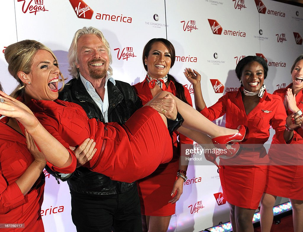 In this handout photo provided by Virgin America Airlines, Virgin Group Founder Sir <a gi-track='captionPersonalityLinkClicked' href=/galleries/search?phrase=Richard+Branson&family=editorial&specificpeople=220198 ng-click='$event.stopPropagation()'>Richard Branson</a> lifts a Virgin America teammate on the red carpet during celebration of launch of new nonstop service from Los Angeles International (LAX) to Las Vegas McCarran International (LAS) Airports, Monday, April 22, 2013, inside The Chandelier at The Cosmopolitan of Las Vegas. The airline celebrates its new flight service with a launch party at The Chandelier at The Cosmopolitan of Las Vegas. The new three daily roundtrip flights from LAX to LAS will add to the airline's existing service from San Francisco and New York to Las Vegas.