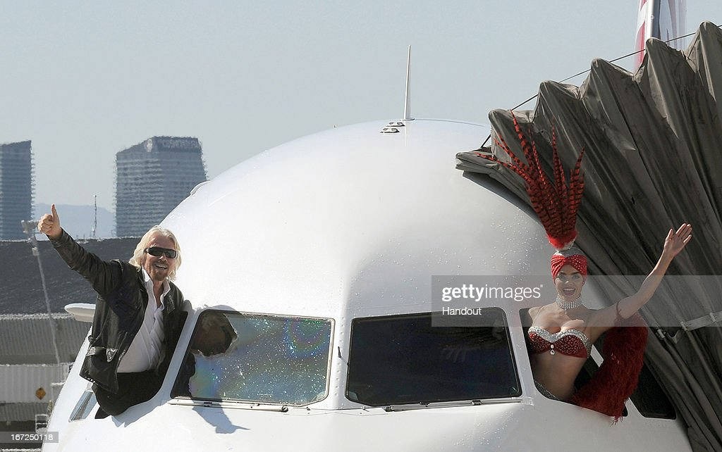 In this handout photo provided by Virgin America Airlines, Virgin Group Founder Sir <a gi-track='captionPersonalityLinkClicked' href=/galleries/search?phrase=Richard+Branson&family=editorial&specificpeople=220198 ng-click='$event.stopPropagation()'>Richard Branson</a> Ð and a Las Vegas showgirl friend Ð emerge from the flight deck window of Virgin America's just landed inaugural flight from Los Angeles to Las Vegas, as the airline celebrates the launch of new nonstop service from Los Angeles International (LAX) to Las Vegas McCarran International (LAS) Airport on Monday, April 22, 2013. The new three daily roundtrip flights from LAX will add to the airline's existing service from its San Francisco International Airport home base to Las Vegas and New York's JFK International Airport. (Photo by Bob Riha, Jr./Virgin America via Getty Images) No Sales