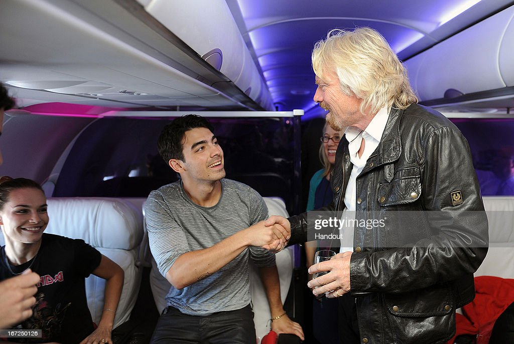 In this handout photo provided by Virgin America Airlines, Virgin Group Founder Sir <a gi-track='captionPersonalityLinkClicked' href=/galleries/search?phrase=Richard+Branson&family=editorial&specificpeople=220198 ng-click='$event.stopPropagation()'>Richard Branson</a> welcomes musician <a gi-track='captionPersonalityLinkClicked' href=/galleries/search?phrase=Joe+Jonas&family=editorial&specificpeople=842712 ng-click='$event.stopPropagation()'>Joe Jonas</a> in-flight during the launch of Virgin America's new nonstop service from Los Angeles International (LAX) to Las Vegas McCarran International (LAS) Airport on Monday, April 22, 2013 at LAX in Los Angeles. To mark the expansion of its Vegas routes, the airline launched a new seat-to-seat cocktail delivery service on flights nationwide, so travelers can send fellow guests onboard a drink and text message via a seatmap on the airline's in-flight entertainment platform.