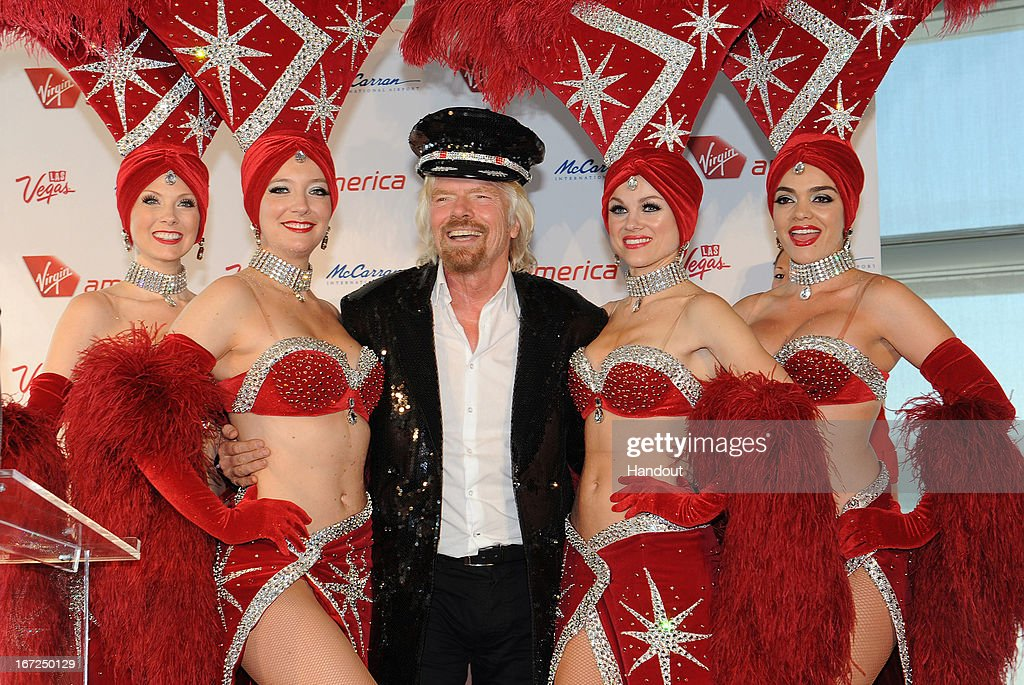 In this handout photo provided by Virgin America Airlines, Virgin Group Founder Sir <a gi-track='captionPersonalityLinkClicked' href=/galleries/search?phrase=Richard+Branson&family=editorial&specificpeople=220198 ng-click='$event.stopPropagation()'>Richard Branson</a> pose for a photo after being presented a sequined captain's jacket by Las Vegas showgirls during the launch of new nonstop service from Los Angeles International (LAX) to Las Vegas McCarran International (LAS) Airport, on April 22, 2013 in Las Vegas, Nevada. The new three daily roundtrip flights from LAX will add to the airline's existing service from San Francisco and New York to Las Vegas McCarran.