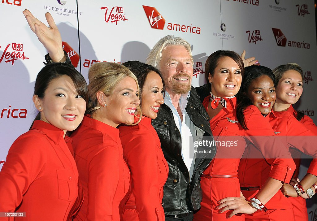In this handout photo provided by Virgin America Airlines, Virgin Group Founder Sir <a gi-track='captionPersonalityLinkClicked' href=/galleries/search?phrase=Richard+Branson&family=editorial&specificpeople=220198 ng-click='$event.stopPropagation()'>Richard Branson</a> is joined by Virgin America teammates on the red carpet during celebration of launch of new nonstop service from Los Angeles International (LAX) to Las Vegas McCarran International (LAS) Airports, Monday, April 22, 2013, inside The Chandelier at The Cosmopolitan of Las Vegas. The airline celebrates its new flight service with a launch party at The Chandelier at The Cosmopolitan of Las Vegas. The new three daily roundtrip flights from LAX to LAS will add to the airline's existing service from San Francisco and New York to Las Vegas.