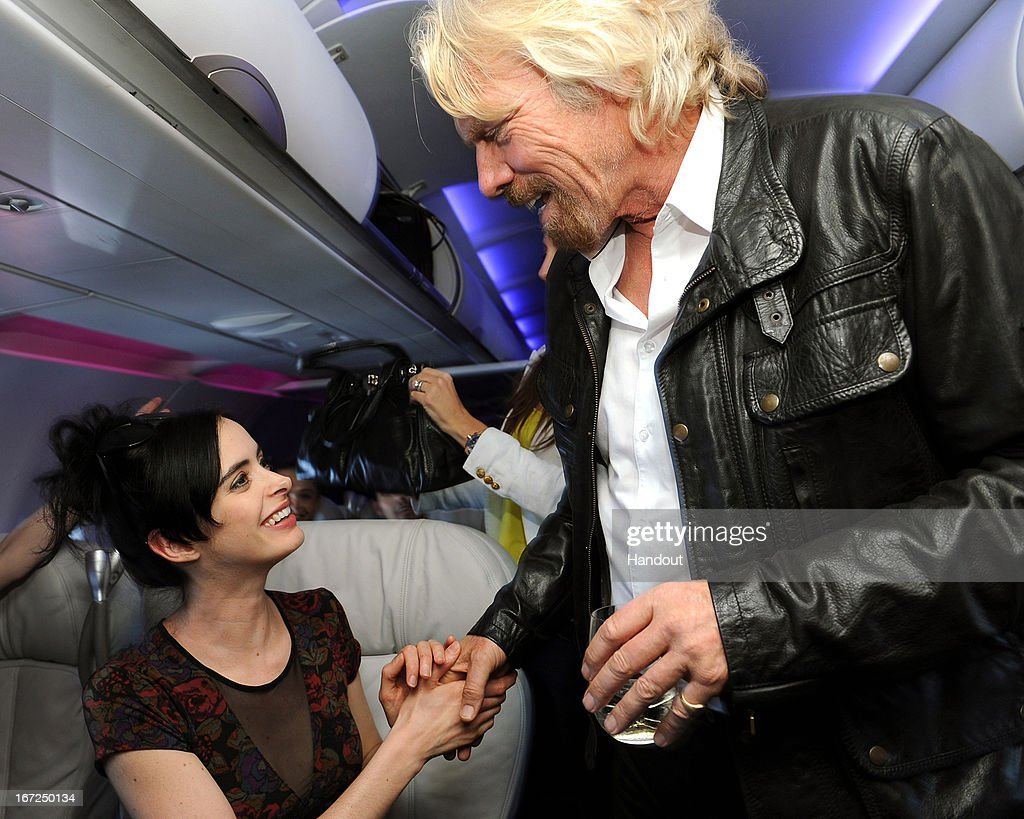 In this handout photo provided by Virgin America Airlines, Virgin Group Founder Sir <a gi-track='captionPersonalityLinkClicked' href=/galleries/search?phrase=Richard+Branson&family=editorial&specificpeople=220198 ng-click='$event.stopPropagation()'>Richard Branson</a> welcomes actress <a gi-track='captionPersonalityLinkClicked' href=/galleries/search?phrase=Krysten+Ritter&family=editorial&specificpeople=655673 ng-click='$event.stopPropagation()'>Krysten Ritter</a> in-flight during the launch of Virgin America's new nonstop service from Los Angeles International (LAX) to Las Vegas McCarran International (LAS) Airport on Monday, April 22, 2013 at LAX in Los Angeles. To mark the expansion of its Vegas routes, the airline launched a new seat-to-seat cocktail delivery service on flights nationwide, so travelers can send fellow guests onboard a drink and text message via a seatmap on the airline's in-flight entertainment platform.
