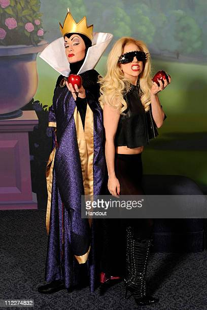 In this handout photo provided by Walt Disney World Grammy Awardwinning singer Lady Gaga poses with the Evil Queen from Disney's animated film 'Snow...