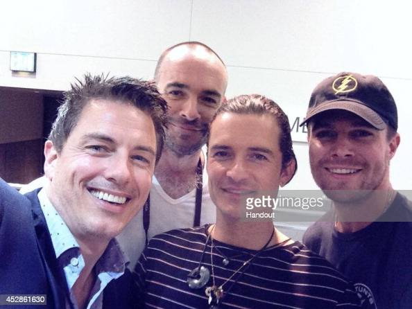 In this handout photo provided by Warner Bros 'Arrow' star Stephen Amell and fellow cinematic archer Orlando Bloom pose for a group selfie with...